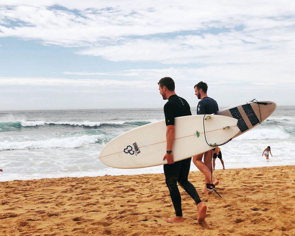 two-men-carrying-surfboards-near-seashore